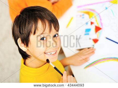 A cute little boy is drawing and being creative with brush