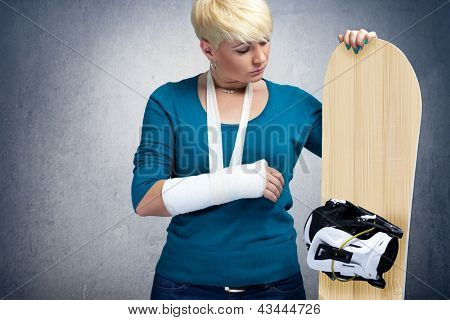 Unhappy snowboarder with  broken arm looking at snowboard
