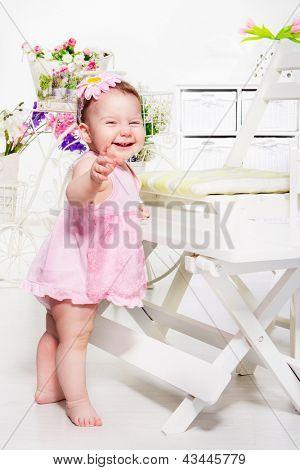Lovely emotional toddler girl in pink dress