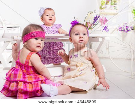 Cute babies beside white wooden bench