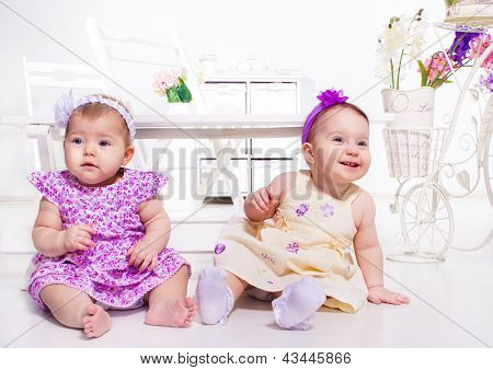 Two baby girls sit on the floor