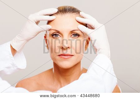 doctor doing skin check on middle aged woman before cosmetic surgery