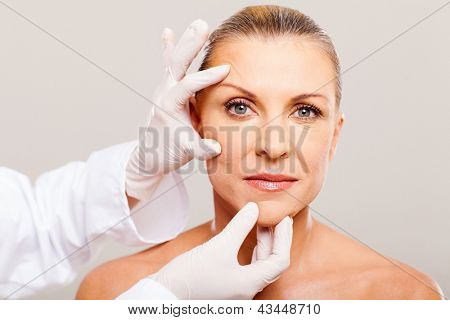 surgeon doing skin check on mid age woman before plastic surgery