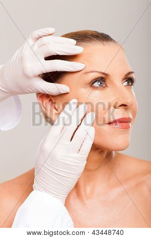 dermatologist checking mature woman face skin
