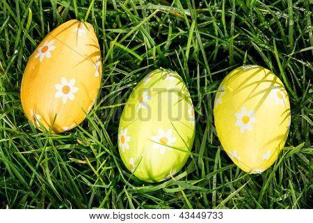 Three easter eggs nestled in the grass overhead shot