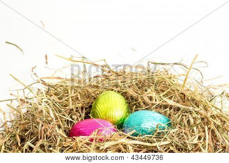 Three easter eggs nestled in straw nest with copy space