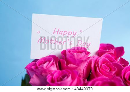 Bouquet of pink roses with mothers day card on blue background