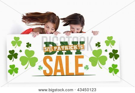 Girls holding placard with st patricks day sale text in green white and orange with shamrocks