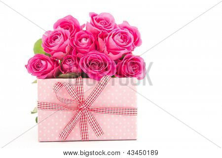 Bouquet of pink roses next to a pink gift on a white background close up