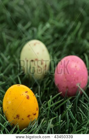 Three small easter eggs nestled in the green grass
