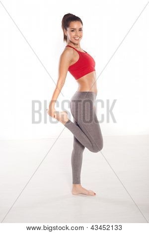 Smiling fit woman stretching her legs in a side view image