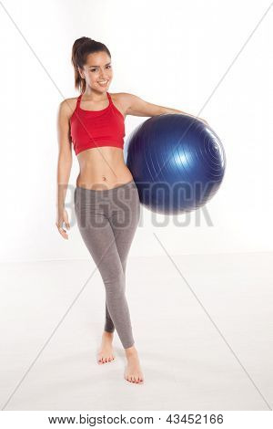 Happy shapely young girl posing with a pilates ball under her arm smiling at the camera on a white studio background