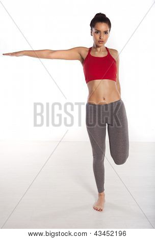 Woman doing balancing exercises standing on one foot with her arm extended outwards to the side isolated studio portrait