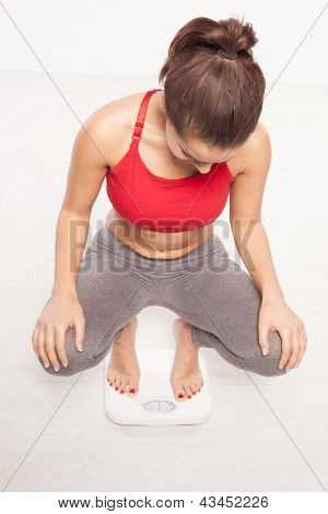 Woman crouching down on a bathroom scale to read her weight, high angle studio portrait looking down at the display