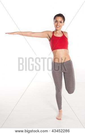 Graceful slender woman stretching her arms over the white background