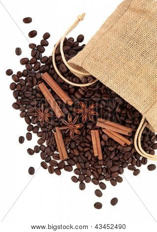 Coffee beans, cinnamon sticks with star anise spice in a hessian drawstring sack  over white background.