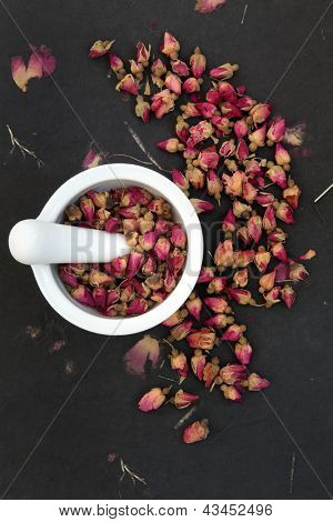 Rosebud flower heads in a white mortar with pestle over rose impregnated black paper, used in chinese herbal medicine.
