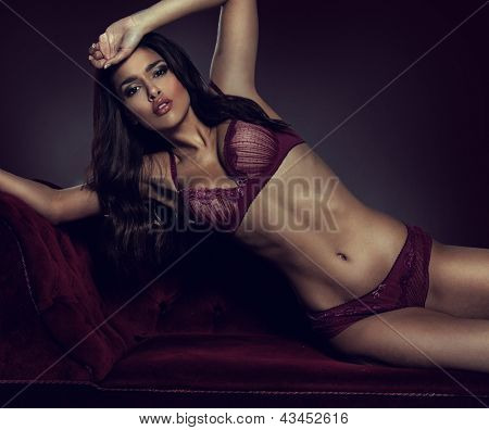Sexy, sultry woman posing in purple lingerie on a purple couch