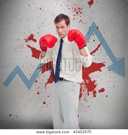 Businessman in boxing gloves against blue loss arrow and blood spatter on a wall