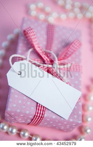 Pink gift wrapped box with blank tag and pearls on pink surface