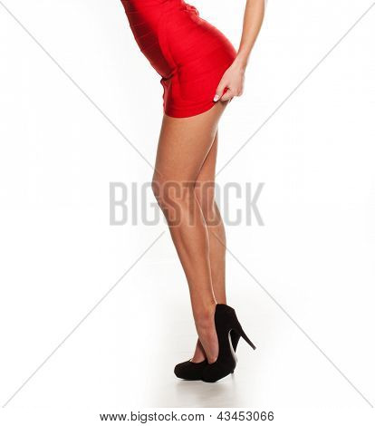 Cropped view of a woman in stilettos with sexy long slender legs and a cute bum in a skimpy red miniskirt against a white studio background