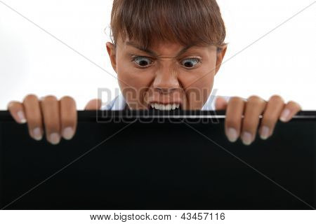 Businesswoman biting laptop screen