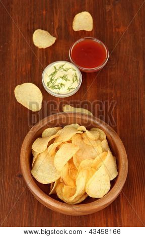 Potato chips  in wooden bowl and sauces, on wooden background