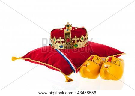 Golden crown on red velvet pillow for coronation in Holland with pair of wooden shoes