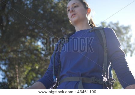 Frontal centered close up of woman hiking in blue shirt facing left