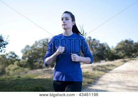 Centered close up of woman jogging outside, facing left
