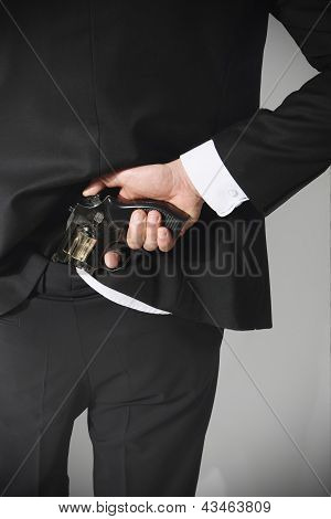 A man conceals a firearm in the back of his pants.