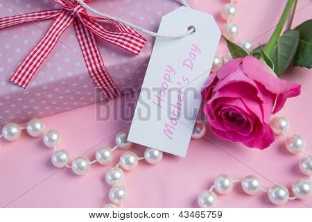 Pink rose with gift and string of pearls and tag for mothers day on pink surface