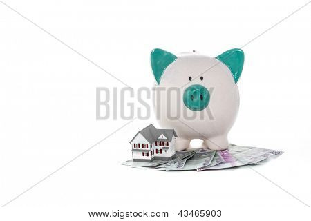 Hand painted piggy bank sitting on pile of dollars with mini house on