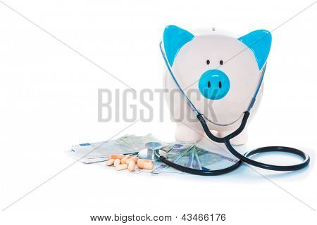Piggy bank sitting on pile of dollars with stethoscope and pills on white background