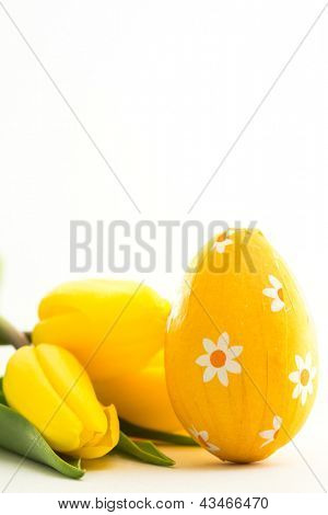 Yellow easter egg with yellow tulips on white background