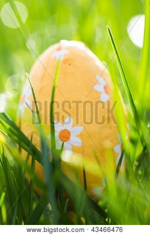 Easter egg wrapped in orange foil nestled in the grass