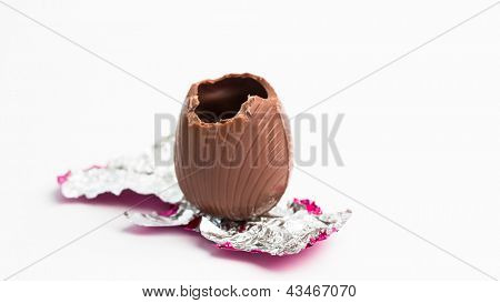 Easter egg unwrapped in pink foil with bite taken out on white background
