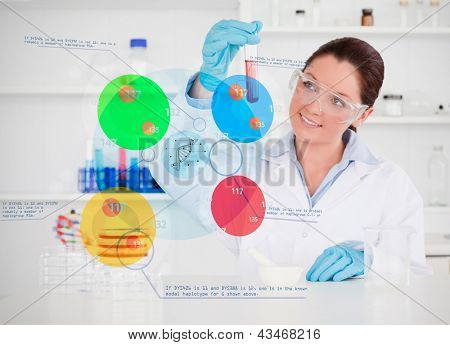 Smiling chemist looking at test tube with colourful holographic interface
