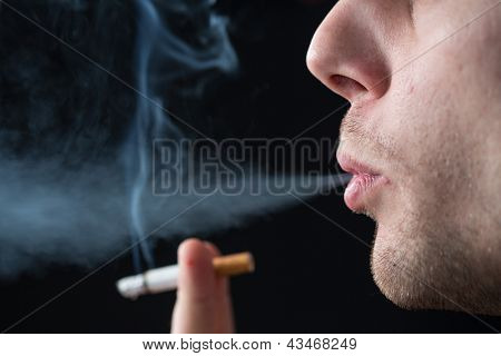 Man exhaling cigarette smoke on black background