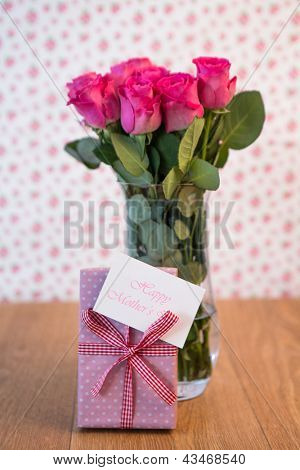 Bunch of pink roses in vase with pink gift leaning against it and mothers day card on wooden table