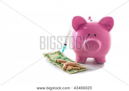 Syringe leaning against piggy bank with dollars and pills on white background