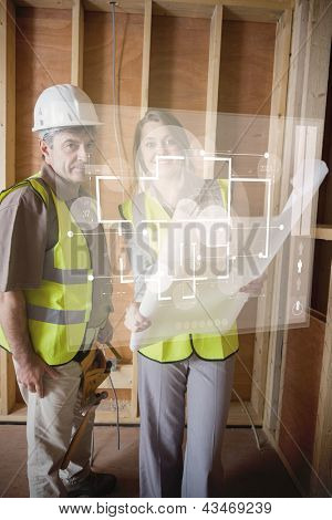 Architect and foreman checking the plans on white interface hologram