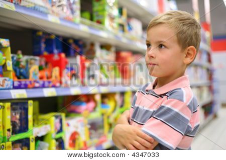 Boy Looks At Shelves With Toys In Shop