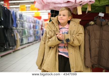 Boy Tries On Jacket In Shop