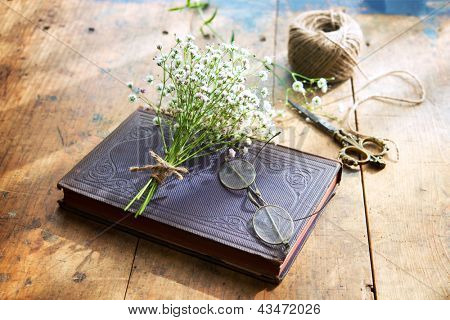 Vintage book, vintage eyeglasses and small bouquet of baby's breath flowers on old worn desk, in warm sunlight by the window.