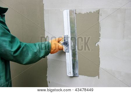 Master makes plaster on a wall
