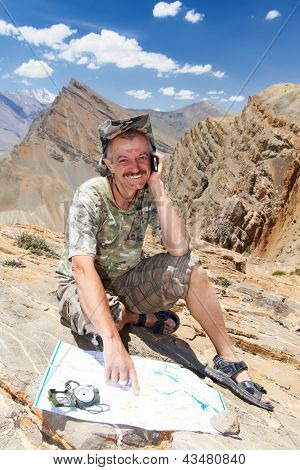 One smiling happy tourist traveller hiker with route map and compass in Himalayas mountains