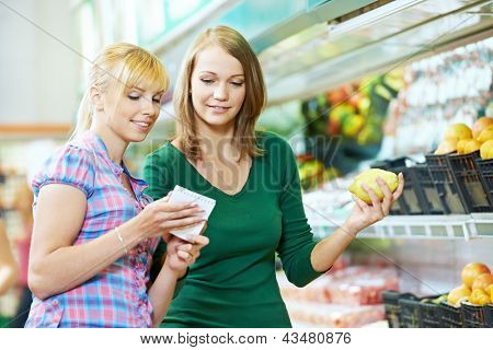 Two woman choosing bio food produces in fruits supermarket with shopping list