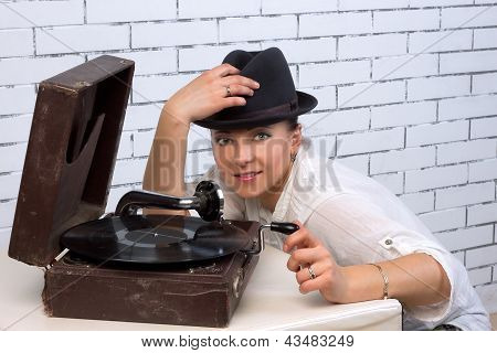 woman in a hat near the gramophone to the plate