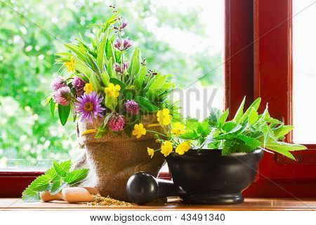Sack With Bouquet Of Healing Herbs And Flowers, Mortar And Pestle On Windowsill